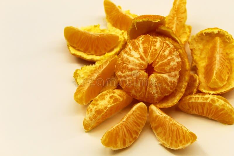 Tangerina descascada na casca da tangerina com fatias no fundo claro foto de stock royalty free