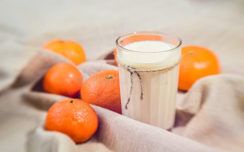 Tangerinas alaranjadas brilhantes e um vidro do leite no fundo de linho da tela fotografia de stock royalty free