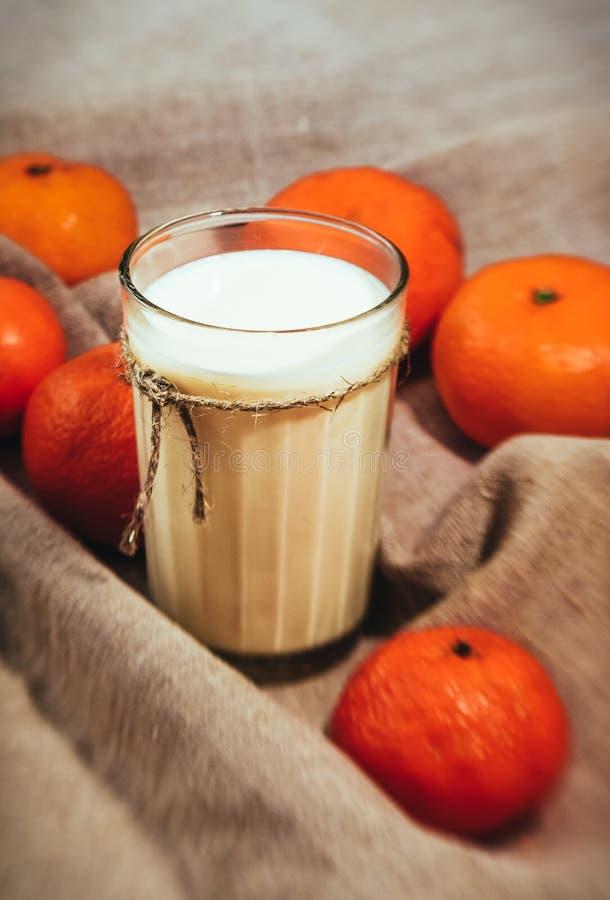 Tangerinas alaranjadas brilhantes e um vidro do leite no fundo de linho da tela fotos de stock royalty free