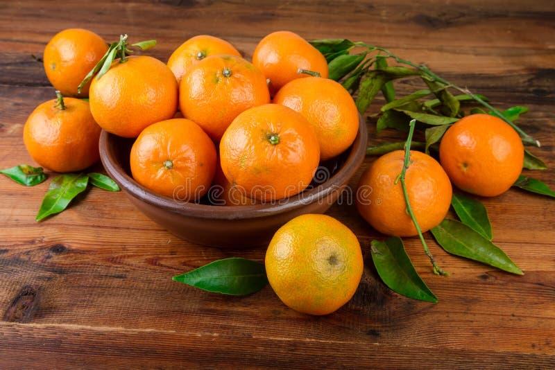 Tangerinas dos mandarino na bacia cerâmica marrom imagens de stock