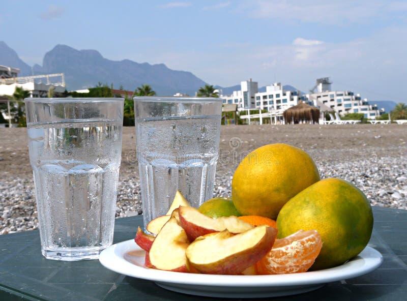 Tangerinas, maçãs com um vidro da água na praia fotografia de stock