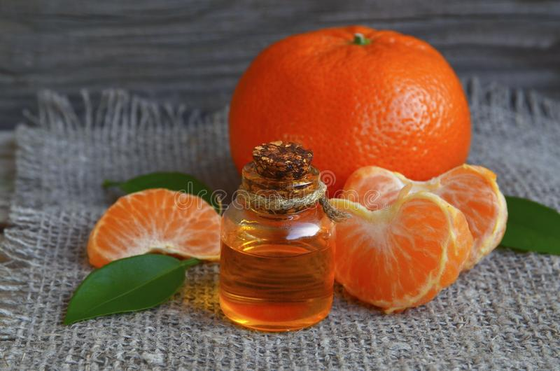Tangerine istotny olej w szklanej butelce z ?wie?? mandarynki owoc na starym drewnianym stole zdjęcia stock