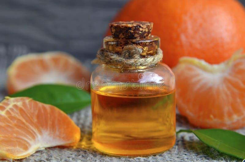 Tangerine istotny olej w szklanej butelce z ?wie?? mandarynki owoc na starym drewnianym stole zdjęcia royalty free
