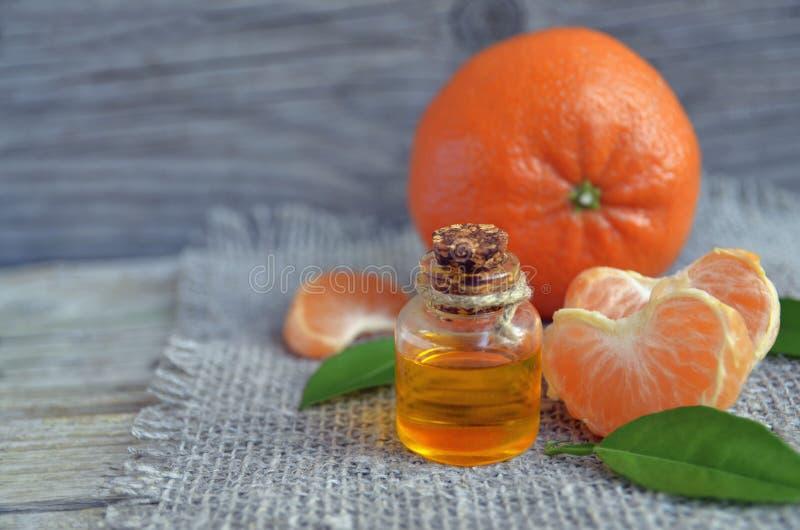 Tangerine istotny olej w szklanej butelce z ?wie?ymi owoc na starym drewnianym stole zdjęcia royalty free
