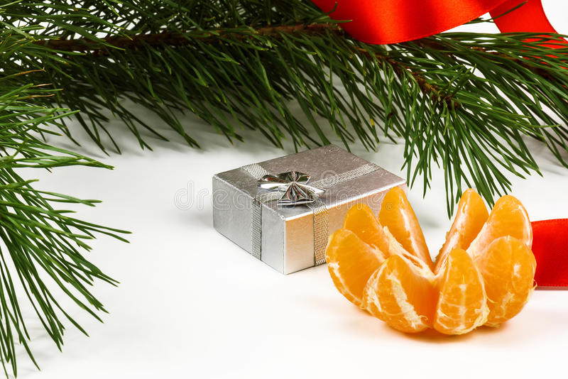 Tangerine, silver box and green pine branches close up. On a white background royalty free stock images