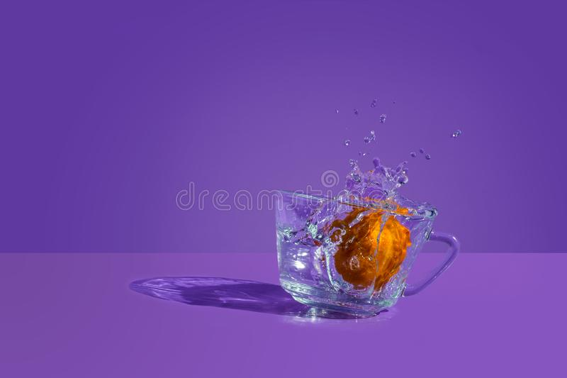 Tangerine Splash. High Speed Photography, tangerine with water splash and sun reflection. Product photography. Original and dinamic fruit photo royalty free stock image