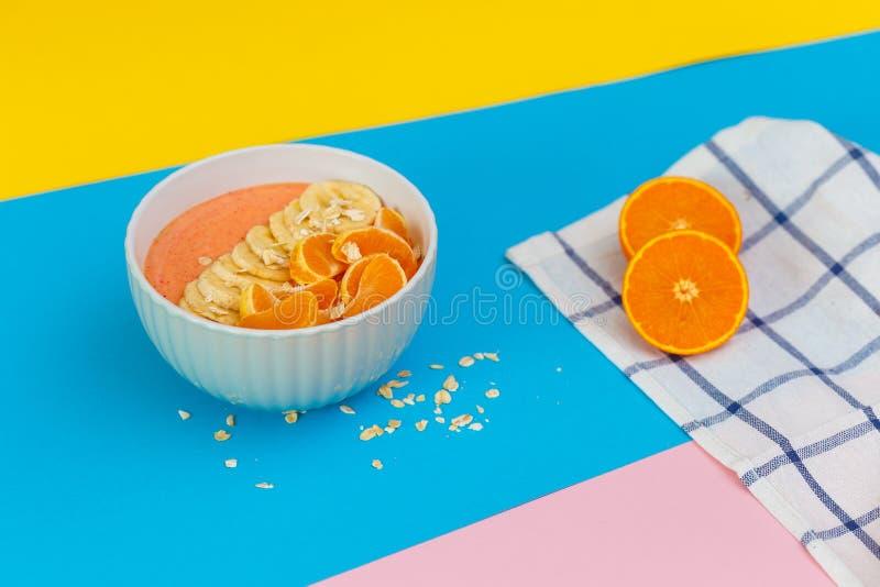 Tangerinen und Bananen auf einer Platte auf farbigen Hintergründen r Beschneidungspfad eingeschlossen lizenzfreies stockbild