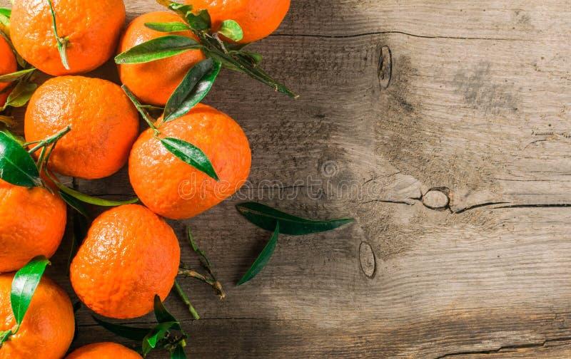Tangerineorangen, Mandarinen, Klementinen, Zitrusfrüchte mit Blättern im Korb über rustikalem hölzernem Hintergrund, Kopienraum stockfotografie