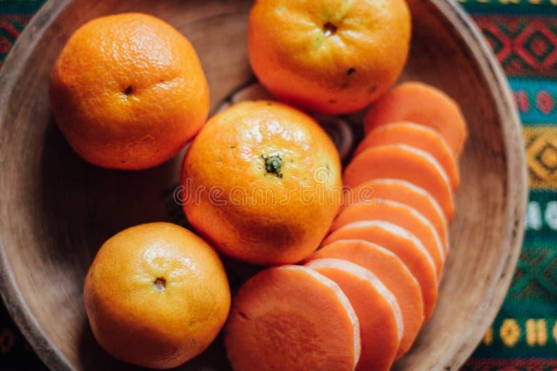 Tangerines και καρότο σε ένα χωμάτινο πιάτο σε ένα φωτεινό τραπεζομάντιλο στοκ εικόνα με δικαίωμα ελεύθερης χρήσης