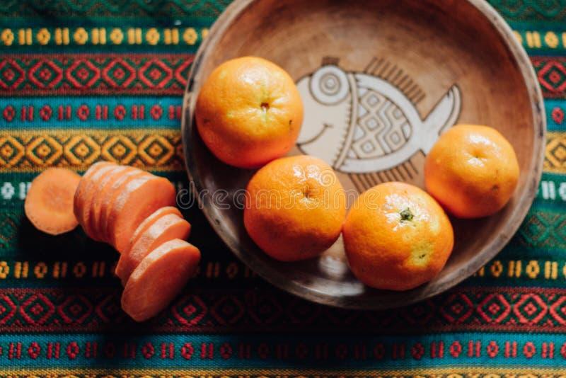 Tangerines και καρότο σε ένα χωμάτινο πιάτο σε ένα φωτεινό τραπεζομάντιλο στοκ εικόνες
