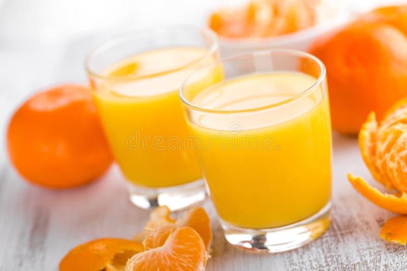 Tangerines, ξεφλουδισμένοι tangerines και tangerine χυμός στο γυαλί Χυμός μανταρινιών στοκ φωτογραφία
