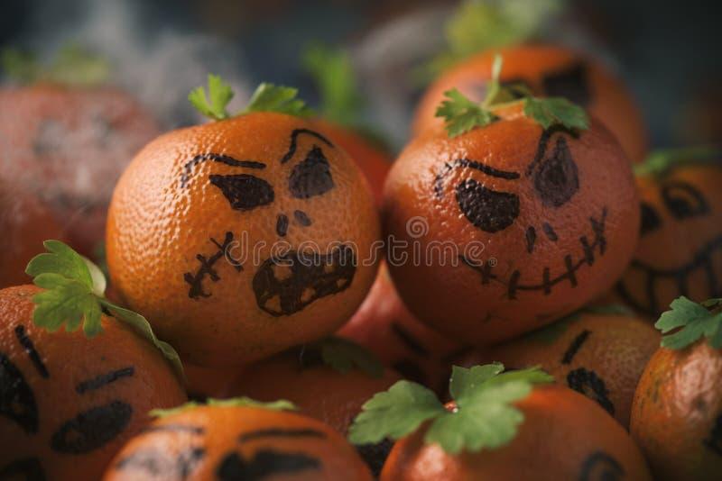 Tangerines που διακοσμούνται ως χαρασμένες κολοκύθες στοκ φωτογραφίες