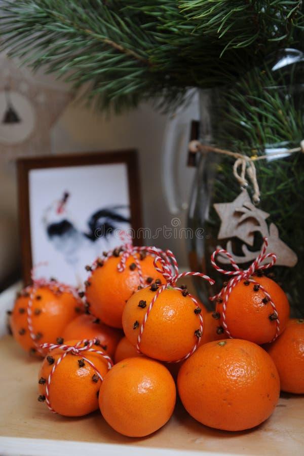 Tangerines, που διακοσμούνται με τα γαρίφαλα και την κόκκινος-άσπρη δαντέλλα Κινηματογράφηση σε πρώτο πλάνο σε ένα υπόβαθρο των κ στοκ φωτογραφία με δικαίωμα ελεύθερης χρήσης