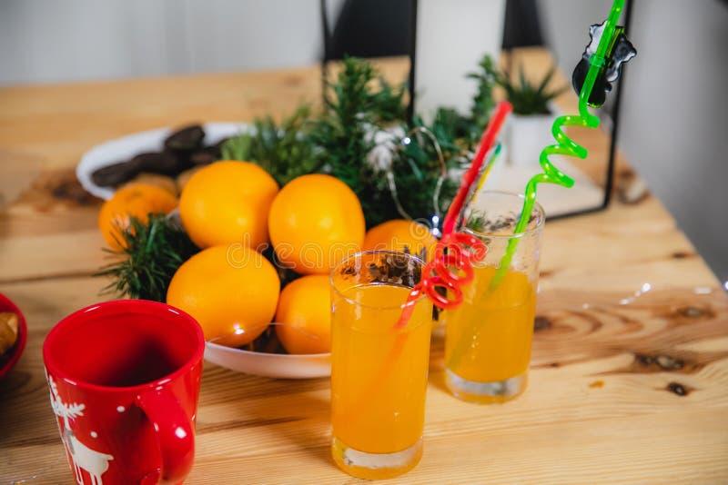 Tangerines, χυμός στα φλυτζάνια γυαλιού και τα σύνεργα Χριστουγέννων στοκ εικόνες