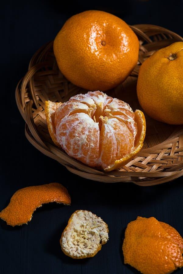 Tangerines в корзине на черном деревянном столе стоковое фото