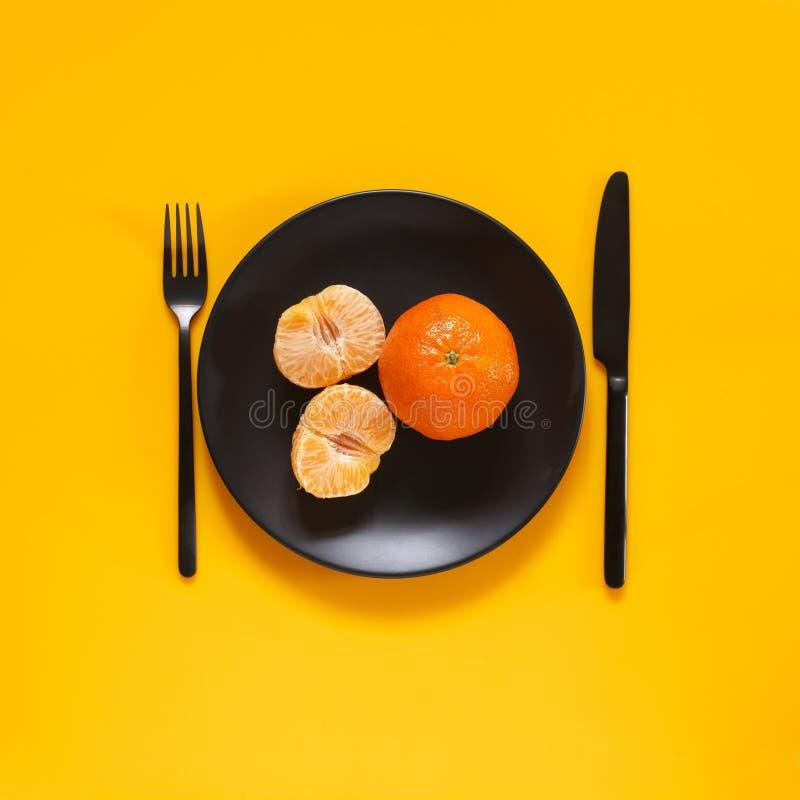 Tangerines в черной плите на желтом цвете стоковые изображения