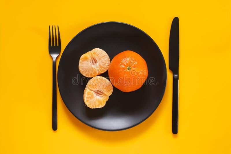 Tangerines в черной плите на желтом цвете стоковое фото rf