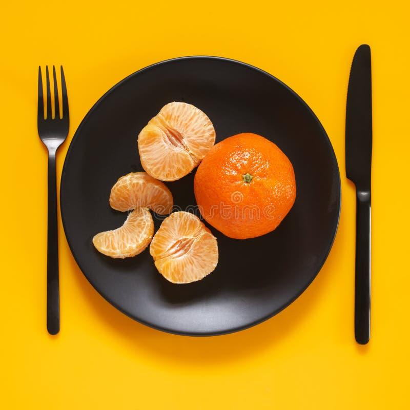 Tangerines в черной плите на желтом цвете стоковая фотография rf
