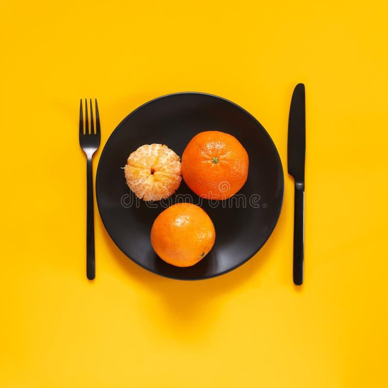 Tangerines в черной плите на желтом цвете стоковое изображение