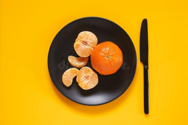Tangerines в черной плите на желтом цвете стоковые фото