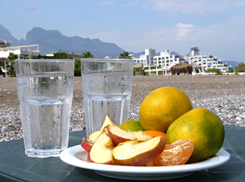 Tangerines, apples with a glass of water on the beach stock photography