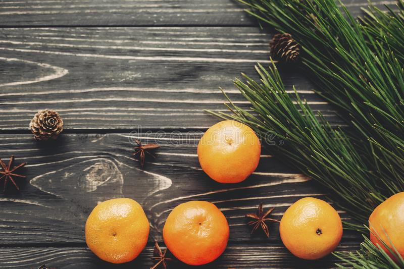 tangerines with green fir branches with cones and anise on rustic wooden background top view with space for text. winter flat lay royalty free stock photography