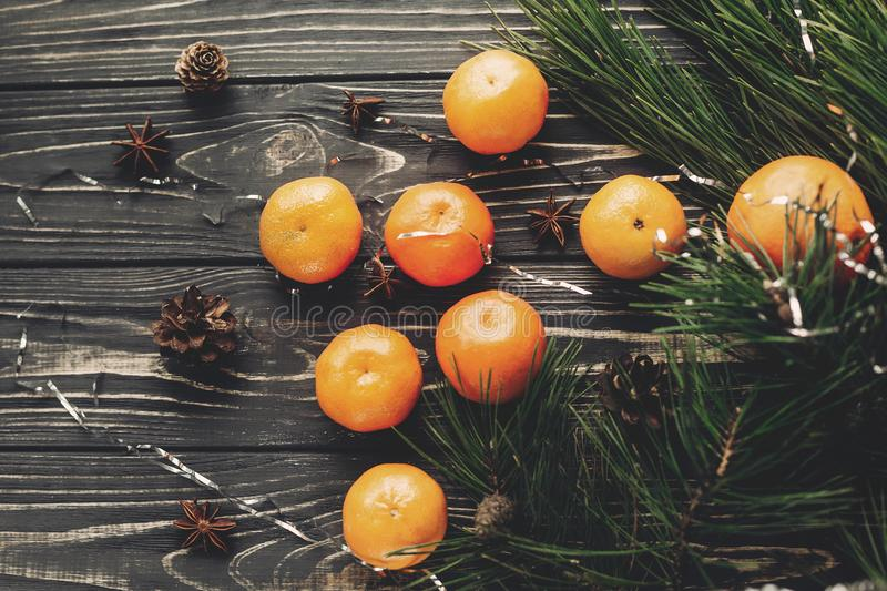 tangerines with green fir branches with cones and anise on rustic wooden background top view with space for text. winter flat lay stock photography