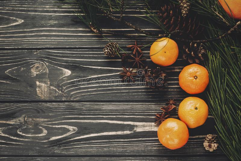 Tangerines with green fir branches with cones and anise on rustic wooden background top view with space for text. winter flat lay. Image, christmas concept royalty free stock photography
