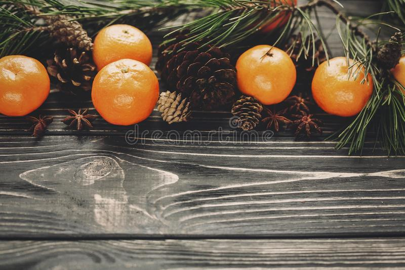 tangerines with green fir branches with cones and anise on rustic wooden background top view with space for text. winter flat lay royalty free stock photos