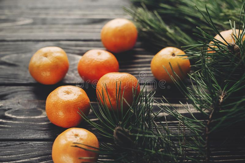 Tangerines with green fir branches with cones on rustic wooden b royalty free stock photos