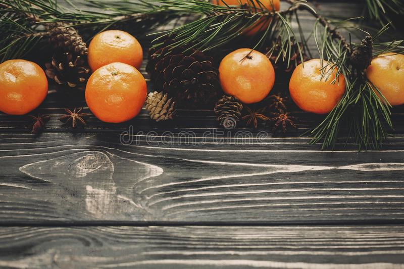 Tangerines with green fir branches with cones on rustic wooden b stock images