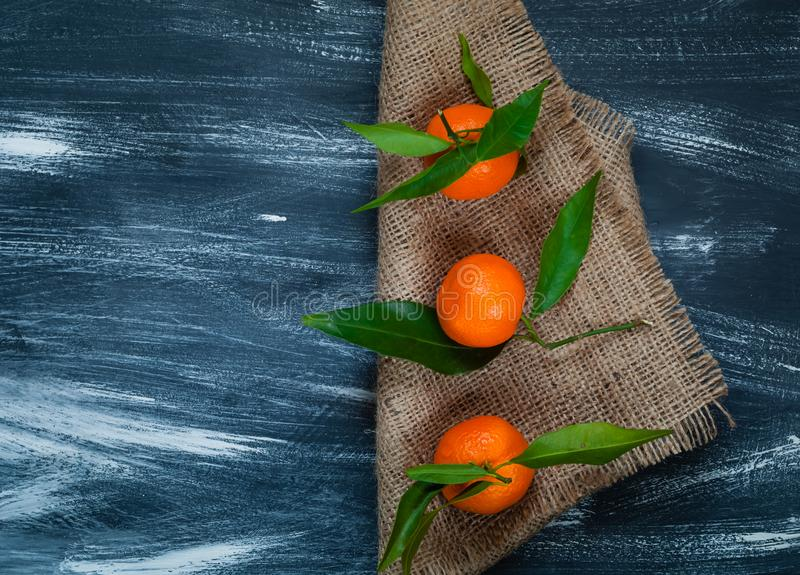 Tangerines with green leaves on burlap on a blue wooden background, closeup, top view, concept of orange fruits royalty free stock images