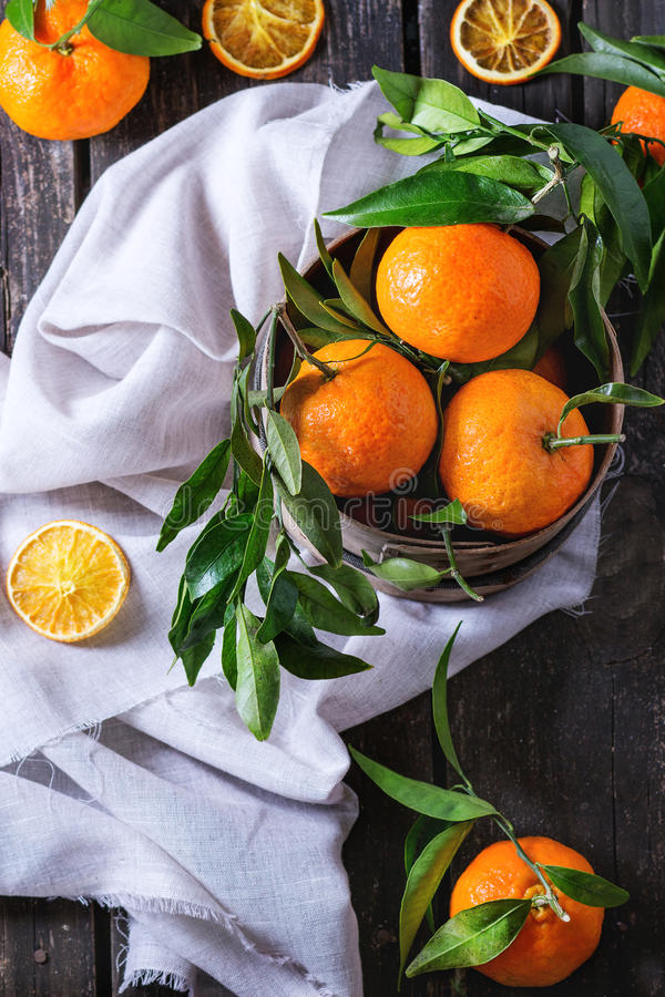 Tangerines with leaves. Bowl of Tangerines with leaves and dry sliced orange on white textile rag over old wooden table. Rustic style. Top view royalty free stock images