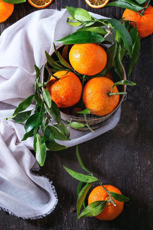 Tangerines with leaves. Bowl of Tangerines with leaves and dry sliced orange on white textile rag over old wooden table. Rustic style. Top view stock photo