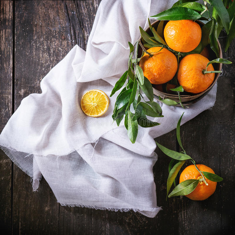 Tangerines with leaves. Bowl of Tangerines with leaves and dry sliced orange on white textile rag over old wooden table. Rustic style. Top view. Square image royalty free stock photo