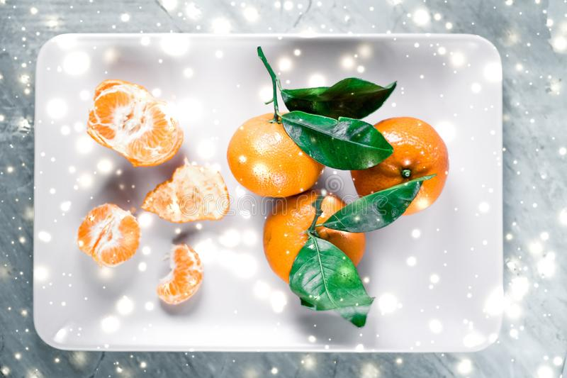 Tangerines, mandarines, clementines in winter holiday time, citrus fruits on plate with glowing snow and glitter on flatlay stock photography
