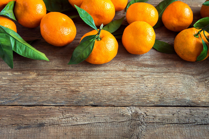Tangerines, oranges. Tangerines oranges, mandarins, clementines, citrus fruits with leaves over rustic wooden background with copy space stock image