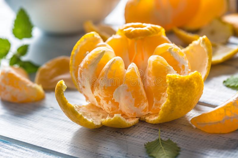 Tangerines with peel and mellisa herbs on table. Ripe fresh tropical fruit on wooden board stock photos