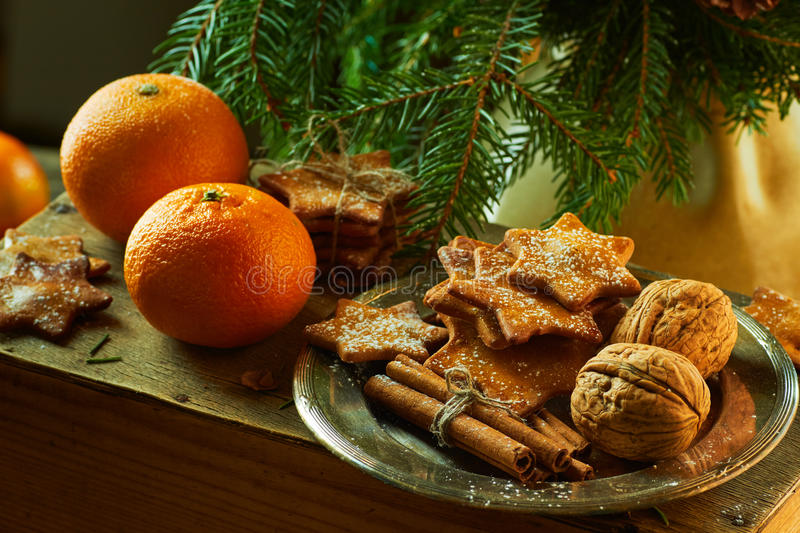 Tangerines and plate with ginger cookies, cinnamon sticks, walnuts on spruce branches background stock photos
