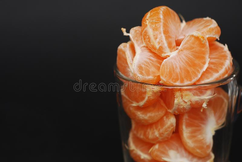 Tangerines Slices in Glass Cup on Black Background. citrus and Vitamine Concept. Copy Space. stock photos