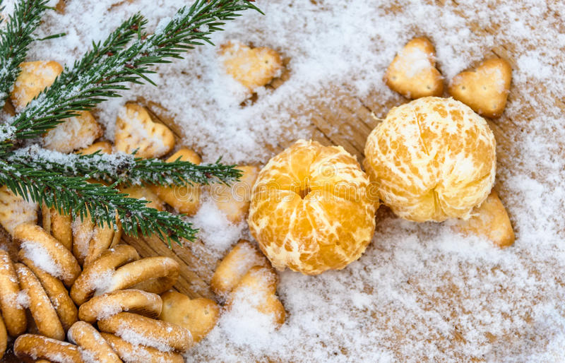 Tangerines in snow on a wooden table, new year, a still life.  royalty free stock images