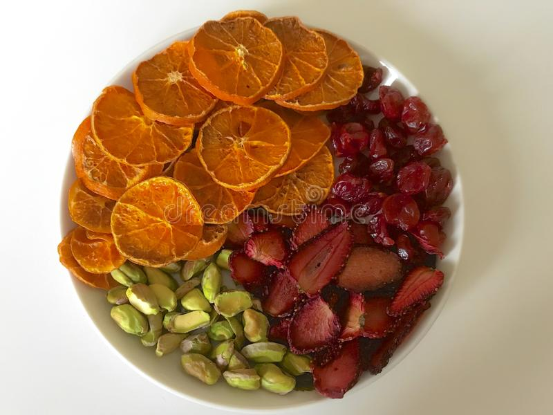 Tangerines and strawberries are cut into slices and dried to decorate desserts. On the plate are also pistachios and dried royalty free stock photos