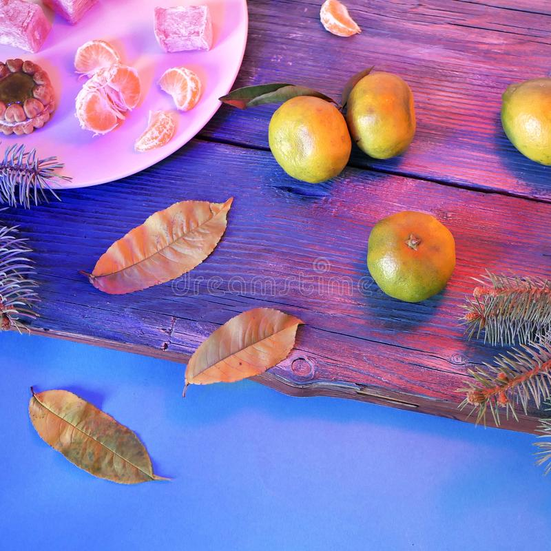 Tangerines, sweets on a dish, leaves, branches of spruce - Christmas still life, new year, seasonal winter holidays, wooden backgr. Ound, purple lighting, top royalty free stock photography