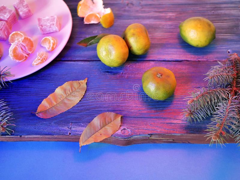 Tangerines, sweets on a dish, leaves, branches of spruce - Christmas still life, new year, seasonal winter holidays, wooden backgr. Ound, purple lighting, top royalty free stock photos