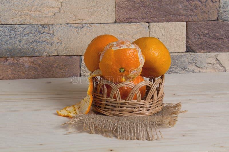 Tangerines w koszu w nieociosanym wnętrzu obrazy stock