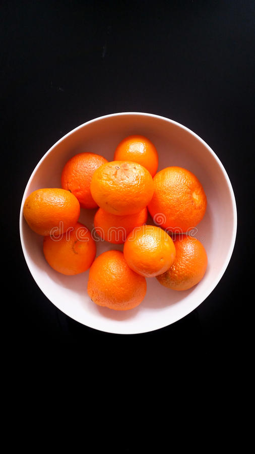 Tangerines in a white bowl on a black background. Tangerines in a white bowl stock photo