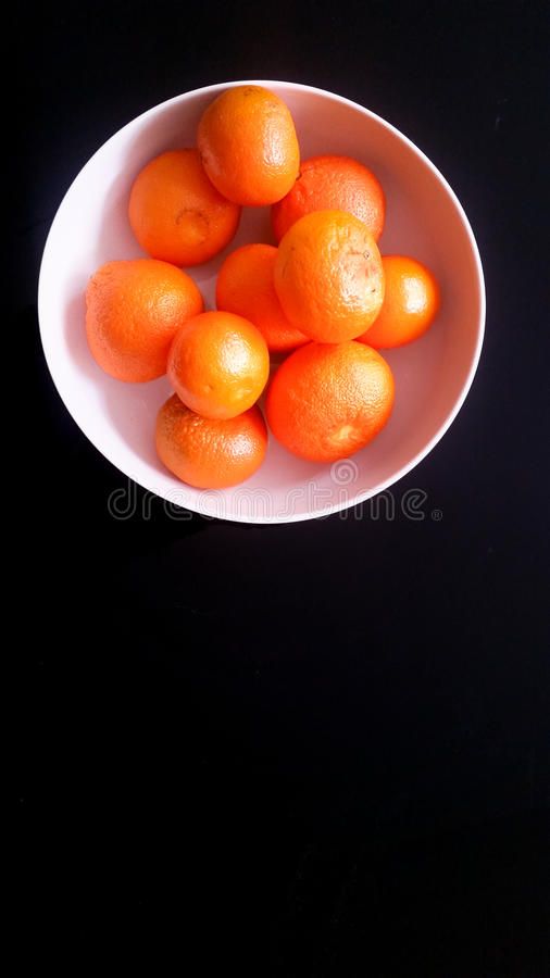 Tangerines in a white bowl on a black background. Tangerines in a white bowl royalty free stock photography
