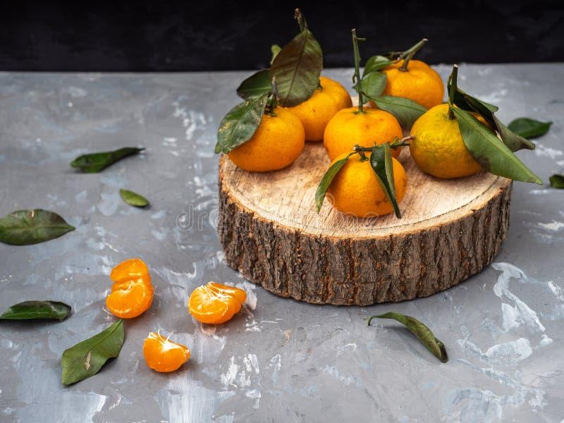 Tangerines z liśćmi na drewnianym dysku, czyścić tangerine Zieleń opuszcza nazbrosany wokoło na szarym tle obraz royalty free