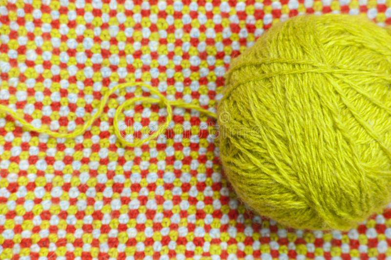 A tangle of green, woolen yarn on a background of knitted, woolen cloth stock images