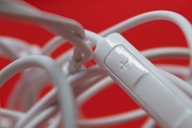 Tangled earphones with the plus button closeup on controller. Image royalty free stock photo